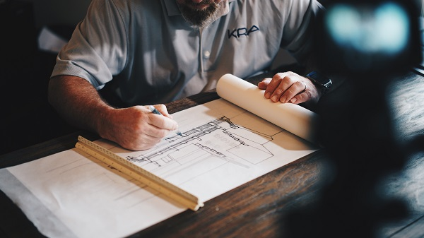 Arkitekt tar fram ritningar för ett byggprojekt.