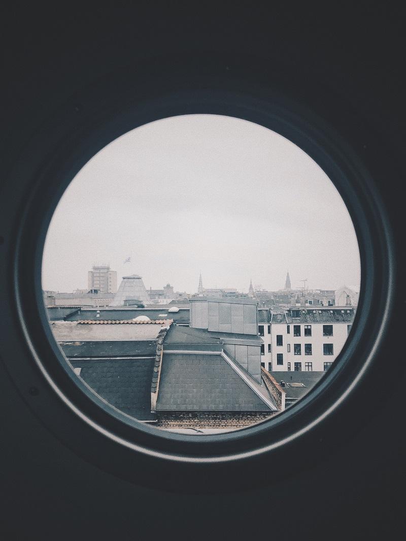 Runt fönster med utsikt över takåsar.