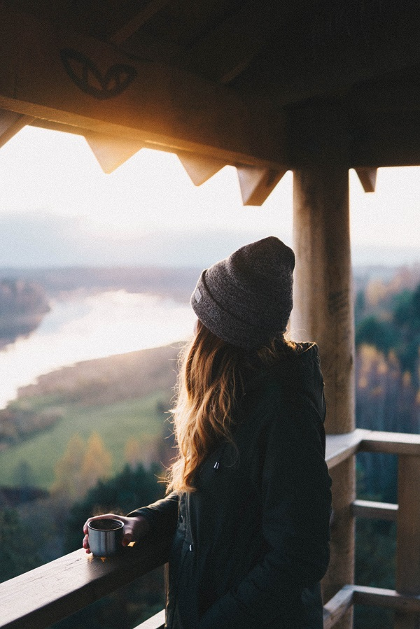 Kvinna njuter av utsikten och en kopp kaffe på sin balkong.
